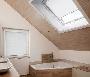 Ein Dachfenster mit einem weissen Plissee